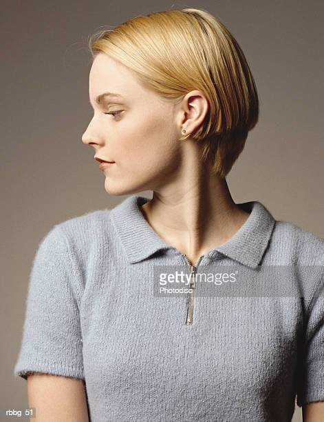 blonde woman standing in a gray background in a blue shirt