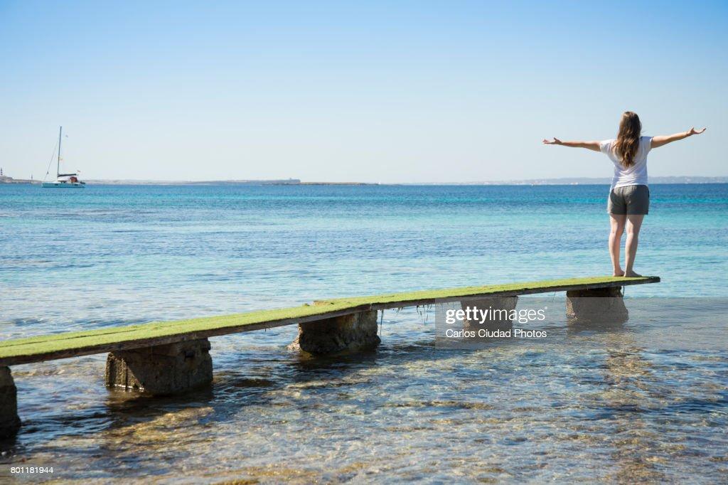 Blonde woman standing on dock with open arms looking at the Mediterranean Sea, Ibiza : Stock Photo