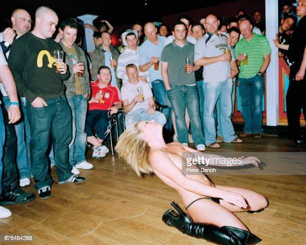 A blonde woman strips in a room full of men at Eden lap dancing club in Blackpool April 2007