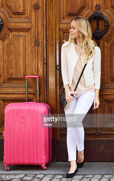 Blonde woman waiting at door with her travelling suitcase