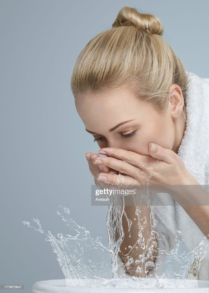 Blonde woman washing her face in bowl : Stock Photo