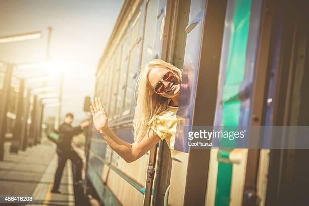 Blonde Frau winkt im Bahnhof