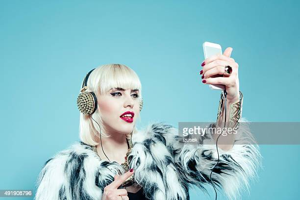 Blonde woman wearing fur jacket taking selfie