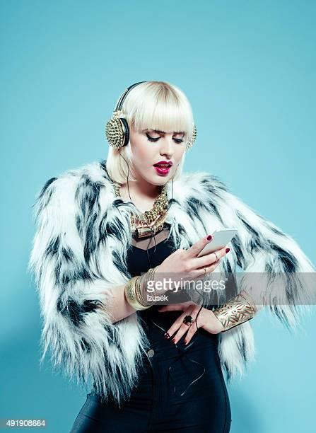 Blonde woman wearing fur jacket using smart phone