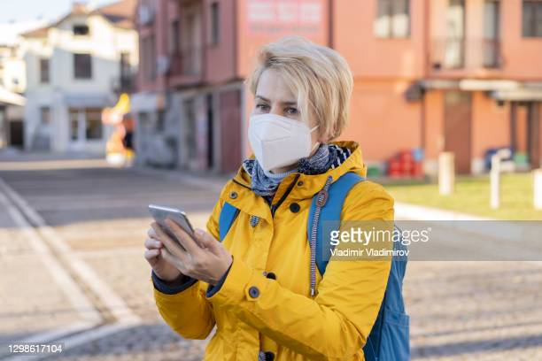 blonde woman wearing protective ffp2 mask using her mobile phone. - department of health and human services stock pictures, royalty-free photos & images