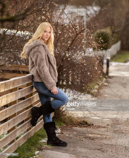blonde woman, winter fur coat, looking at camera - fur coat stock pictures, royalty-free photos & images