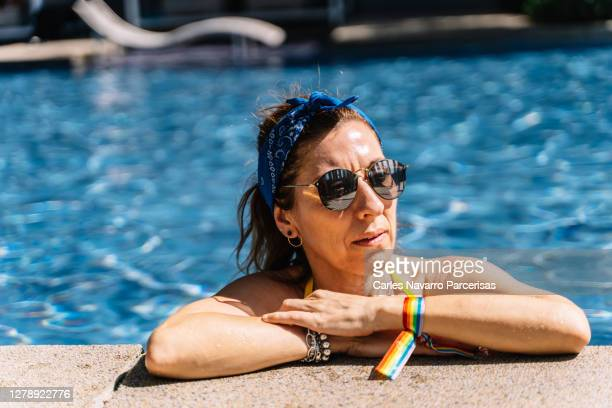 blonde woman with a headband and sunglasses inside the pool leaning on the edge with a rainbow bracelet with the lgtb flag - bisexuality fotografías e imágenes de stock
