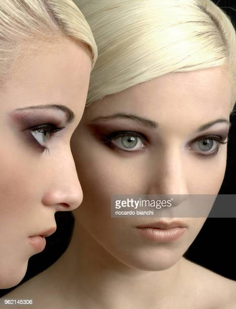 blonde woman with blue and smokey eyes at the mirror - purple eyeshadow stock photos and pictures