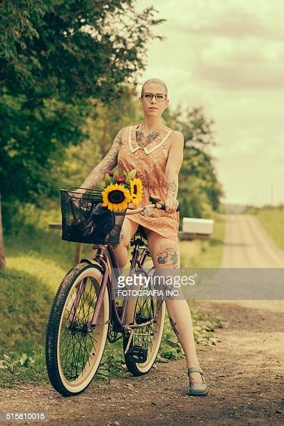 blonde woman with cruiser bicycle - body piercings stock photos and pictures
