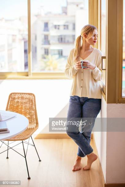 blonde woman with cup of coffee looking out of the window - one young woman only stock pictures, royalty-free photos & images
