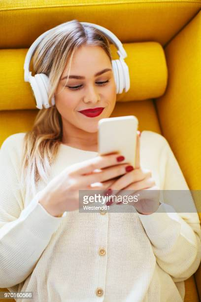 blonde woman with headphones using smartphone at home - bluetooth stock pictures, royalty-free photos & images