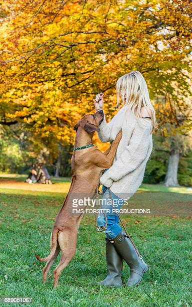 blonde woman with long hair enjoys time with dog