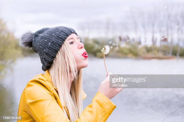 blonde woman with red lips and grey wool cap blowing a dandelion to the right, small particles come out of the dandelion. background with water and trees without autumn leaves. - mois de mai photos et images de collection