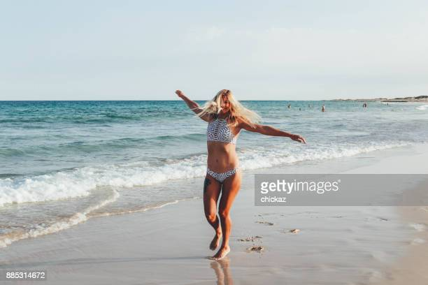blonde frauen tanzen am strand im bikini - blond frauen strand stock-fotos und bilder