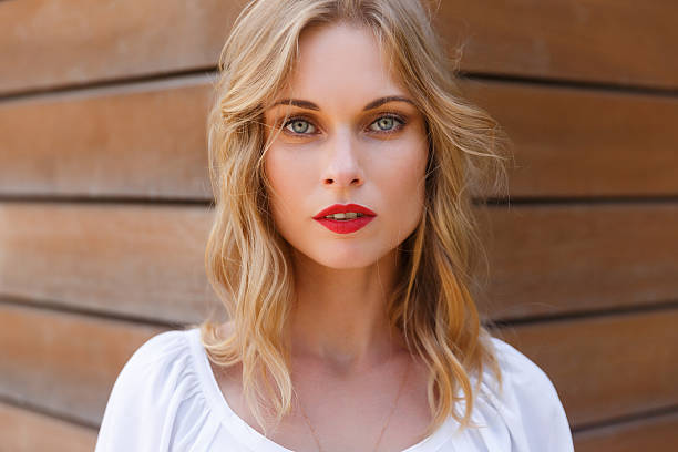 Blonde young woman closeup with gray eyes and red lips