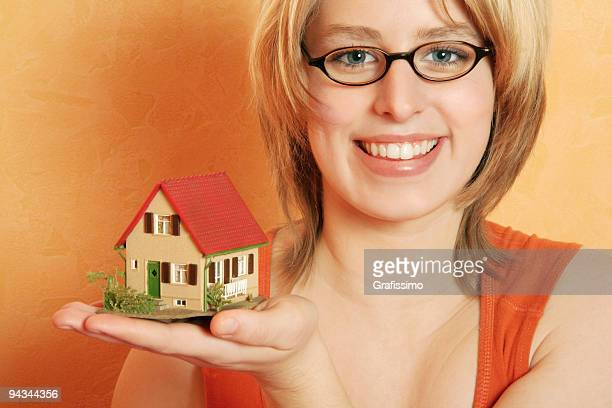 blonde young woman offering a house for real estate - real_property stock pictures, royalty-free photos & images