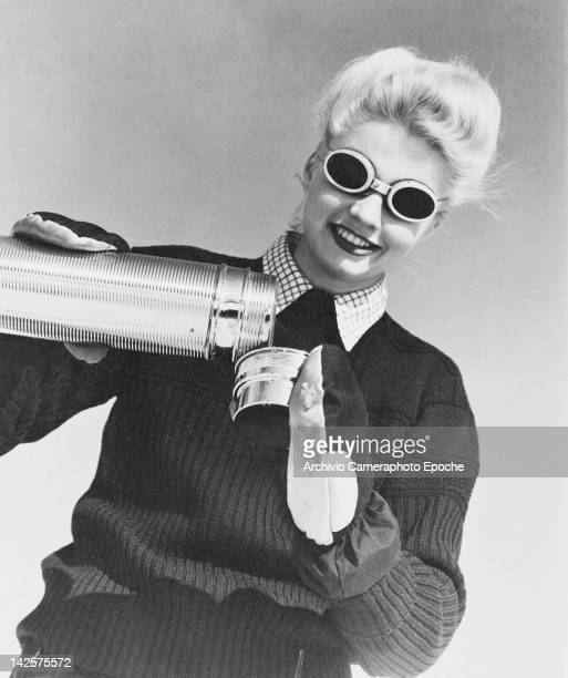 A blonde young woman pours a drink from a thermos flask circa 1948