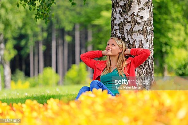 blonde young woman resting near birch in park
