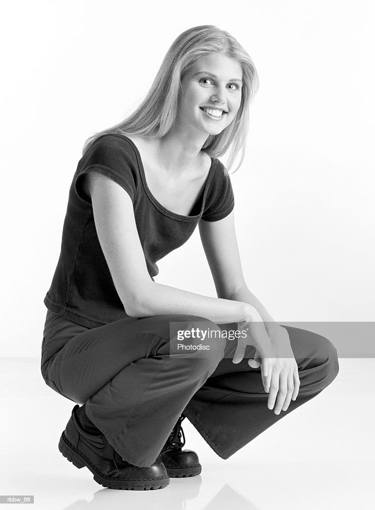 A blonde young woman sits on her heels on the floor : Stockfoto