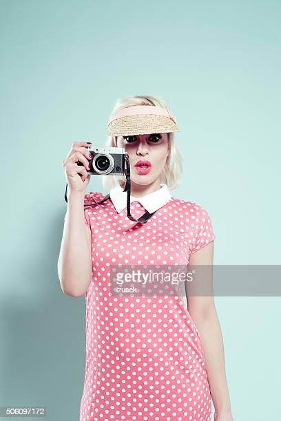 Blonde young woman wearing sunshade cap, holding camera