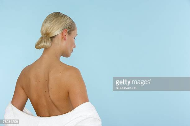 blonde young woman wrapped in a towel, rear view - neo foto e immagini stock