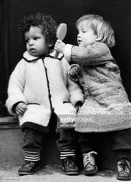 Blondes Mädchen kämmt die Haare ihrer schwarzen Freundin1981