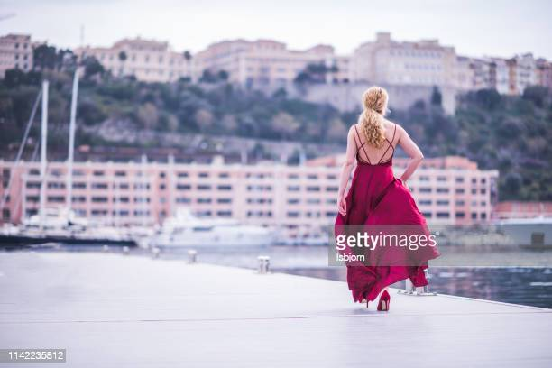 blondie lady in red silk dress running away. - monaco stock pictures, royalty-free photos & images