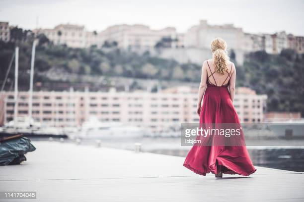 blondie lady walking in red dress. - long dress stock pictures, royalty-free photos & images