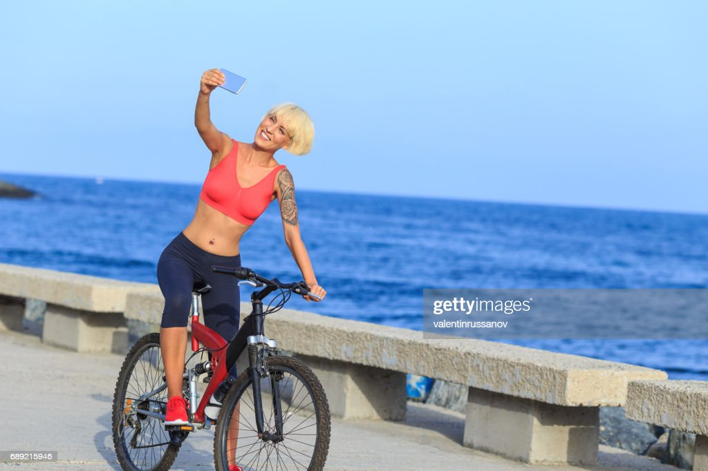 Blong woman riding a bike and taking selfie : Stock Photo