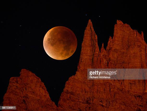 Blood Moon over jagged mountains.