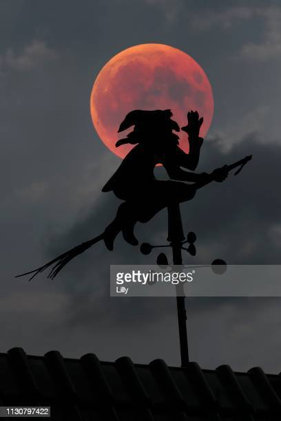 Blood moon over the roof of a house with weather vane with weather witch, Baden-Wuerttemberg, Germany