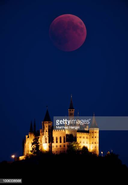 Blood Moon rises behind The Hohenzollern Castle the ancestral seat of the Prussian Royal House and of the Hohenzollern Princes situated at the...