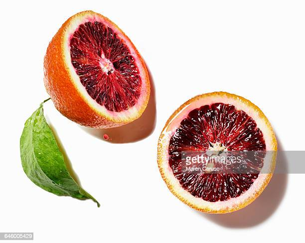 Blood orange halves on white surface