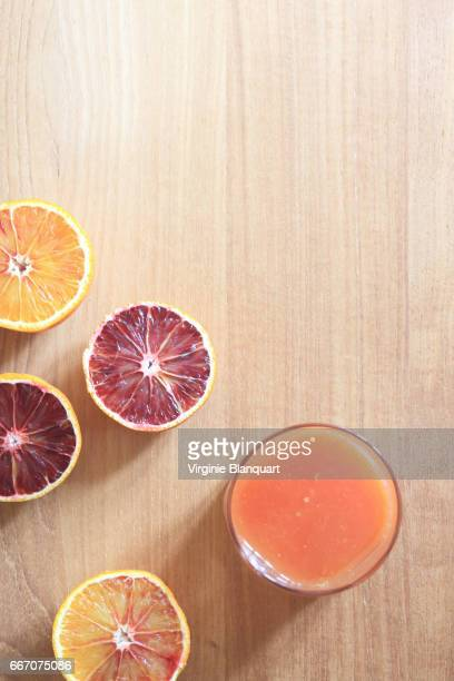Blood oranges cut in half on wooden table