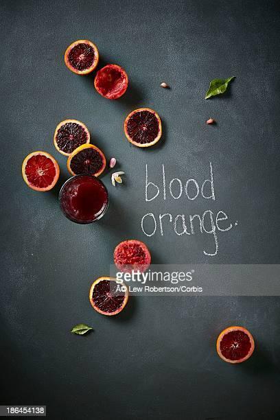 Blood oranges shot overhead on a chalkboard surface.