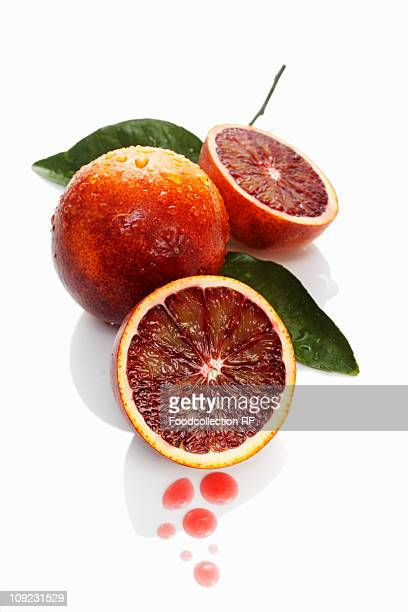 Blood oranges with drops of juice against white background, close-up