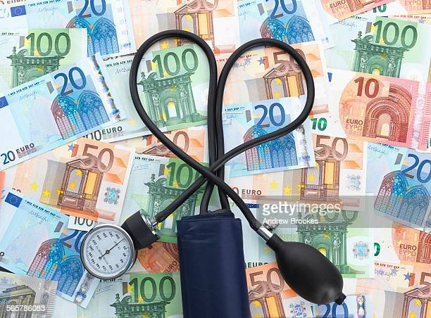 Blood pressure gauge on top of euro currency notes, tubes twisted into heart shape