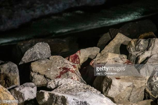 Blood sits on rocks on the shoot after police officers found a suspect involved in a shooting on Redondo Beach Pier on Wednesday, Aug. 25, 2021 in...
