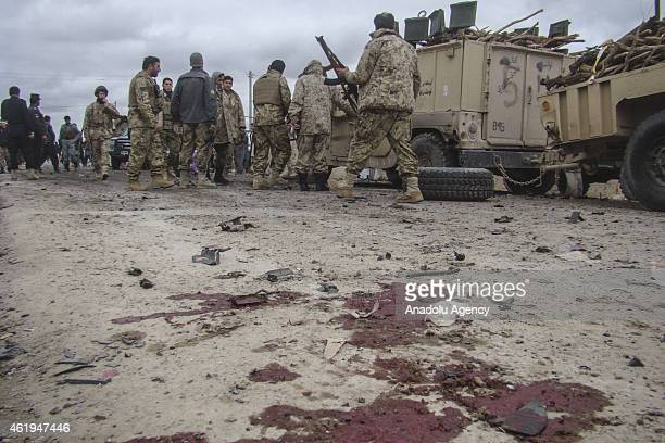 Blood stain is seen on the ground as Afghan security officials inspect the site of a suicide bomb blast that targeted the police vehicle in Helmand...