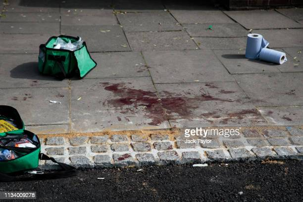 Blood stain lies across the pavement at the scene of a stabbing in Edmonton on March 31, 2019 in London, England. Four people have been stabbed in a...