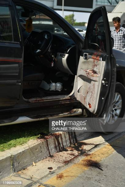 Blood stains are pictured on and next to a damaged vehicle following a mass shooting by the Terminal 21 shopping mall in Nakhon Ratchasima on...