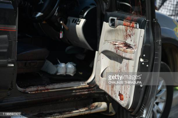 Blood stains are pictured on the door of a damaged vehicle following a mass shooting by the Terminal 21 shopping mall in Nakhon Ratchasima on...