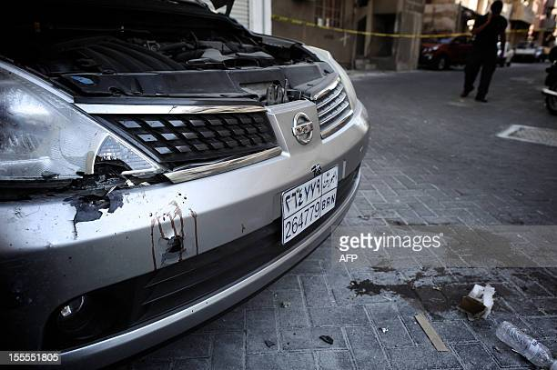 Blood stains are seen on a damaged car at the site of an explosion in the Bahraini capital Manama on November 5 following a series of explosions...