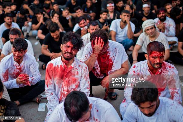 Blood-covered Iraqi Shiites mourners react after flagellating themselves in the southern city of Basra, during the procession on the tenth day of...
