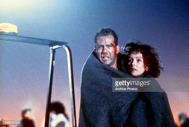 Bloodied Bruce Willis and Bonnie Bedelia wrapped in blanket in a scene from the film 'Die Hard 2' 1990