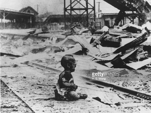A bloodied crying child sitting outside the South Railway Station in Shanghai after a Japanese bombing raid