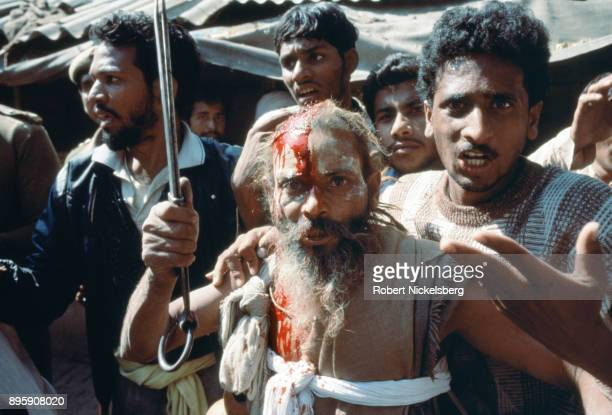 A bloodied Hindu activist raises a sword as he and other Hindu fanatics are stopped by security forces from entering into the Babri Mosque October 30...