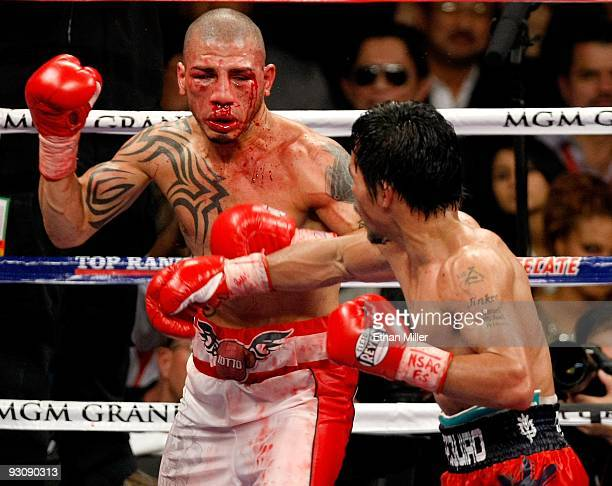 A bloodied Miguel Cotto and Manny Pacquiao battle during the 11th round of their WBO welterweight title fight at the MGM Grand Garden Arena on...