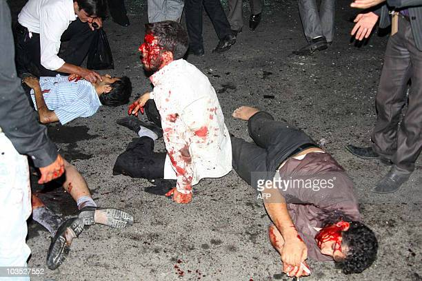 Bloodied victims are seen outside the Jameh mosque in the southeastern Iranian city of Zahedan on July 15 2010 Two suicide bombings at a Shiite...