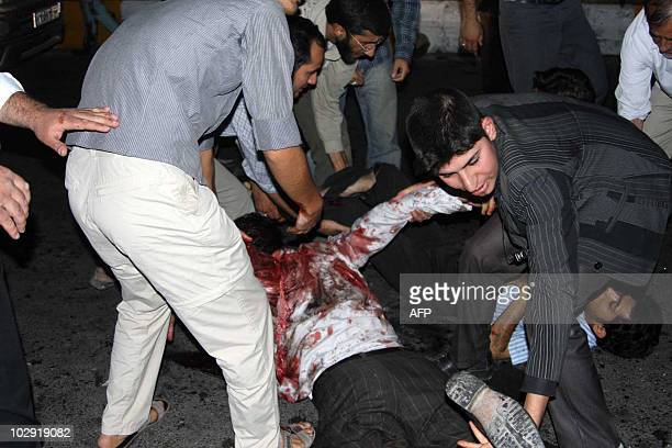 Bloodied victims are tended to outside the Jameh mosque in the southeastern Iranian city of Zahedan on July 15 2010 Two suicide bombings at a Shiite...